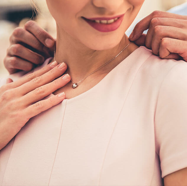 Man placing a necklace around a woman's neck | Gifts